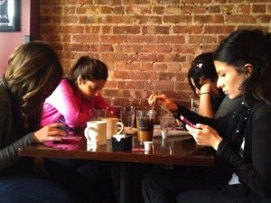 women in cafe using phones