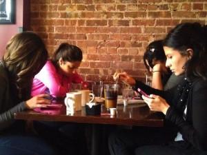 women in cafe using phones